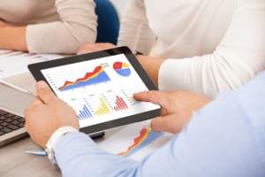 executives-discussing-graphs-on-tablet